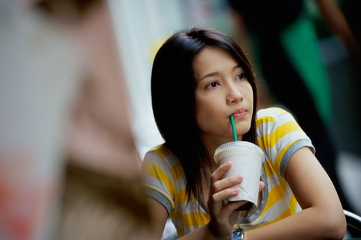 Close-up of a young woman drinking with a drinking straw : Stock Photo