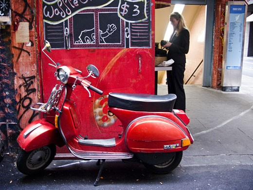 Motor scooter parked beside a store with a woman in the background, Melbourne, Victoria, Australia : Stock Photo