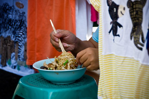 Thailand, woman enjoying version of Pho from in between her items for sale : Stock Photo