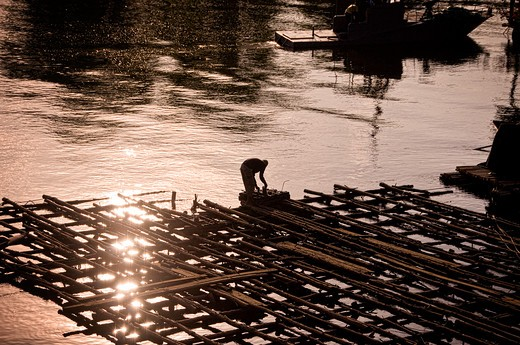 Stock Photo: 1311-2330 Thailand, Silhouette of man on construction on river Kwai at sunset. The Bridge Over The River Kwai still exists today. It is a viable railroad bridge that still carries freight and passenger trains on a daily schedule. It is also a well known tourist locations because of the events of World War II