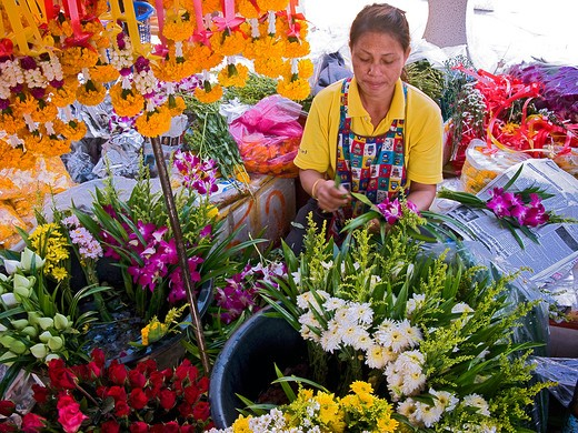 Woman selling flowers in front of buddhist temple : Stock Photo