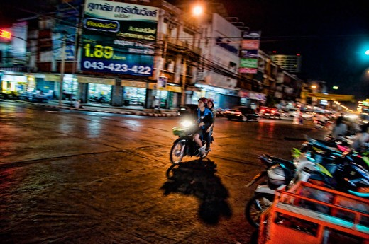 Thailand, Khown Kaen, Two young girls ride through city at night : Stock Photo