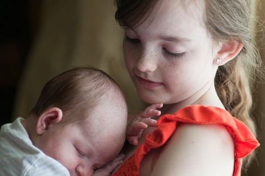 Girl holding baby girl : Stock Photo