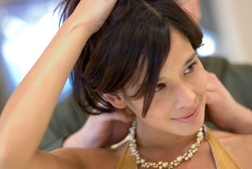 Close-up of a young man putting a necklace around a young woman's neck : Stock Photo