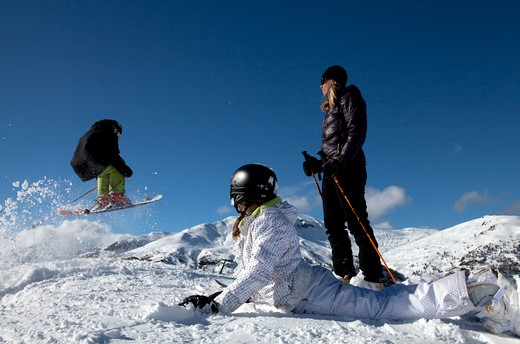 Stock Photo: 1315-1048 Teenage boys skiing with his mother and sister watching at him