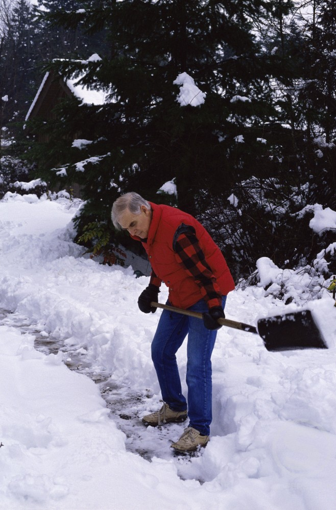 Side profile of a senior man shoveling snow : Stock Photo