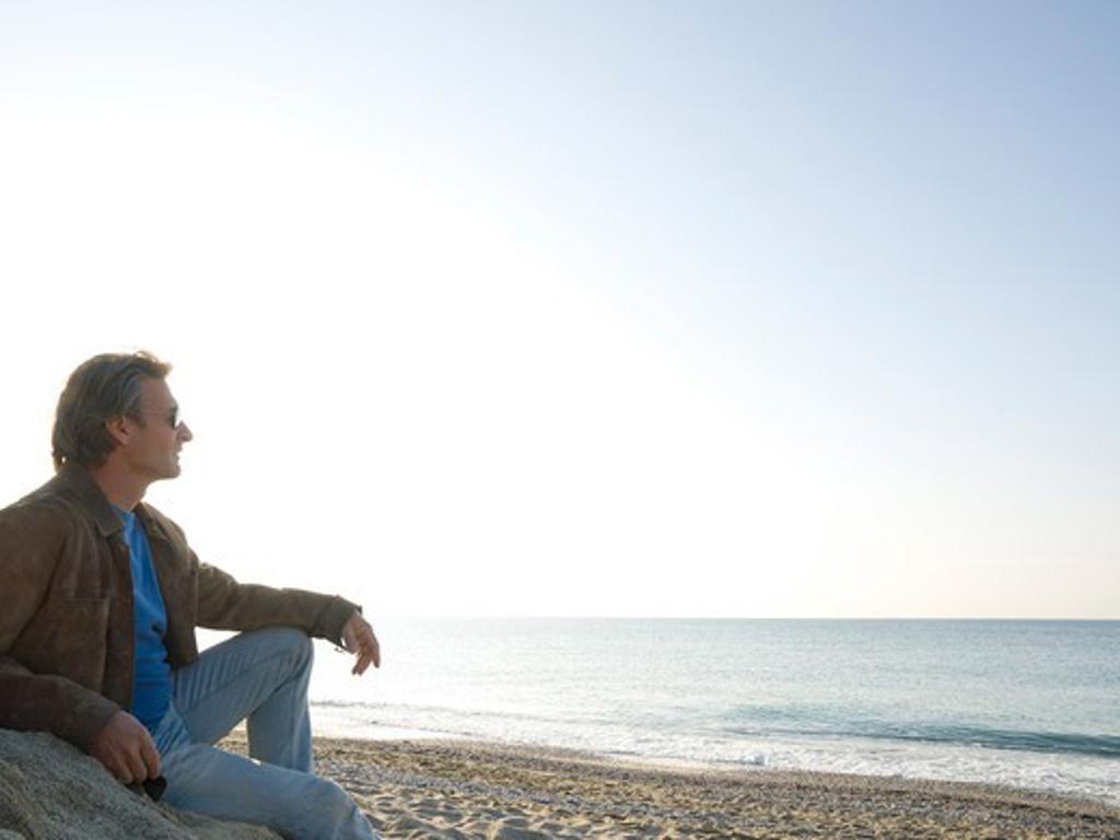 Man sitting on the beach : Stock Photo