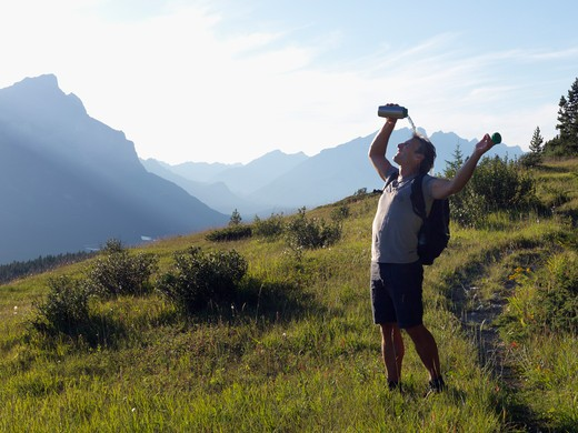 Hiker pouring water over his head, Alberta, Canada : Stock Photo