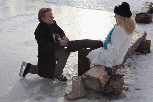 Stock Photo: 1315-1210 Mature man putting on ice skate to his wife, Alberta, Canada