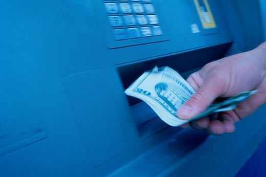 Close-up of a person's hand withdrawing cash from an ATM : Stock Photo
