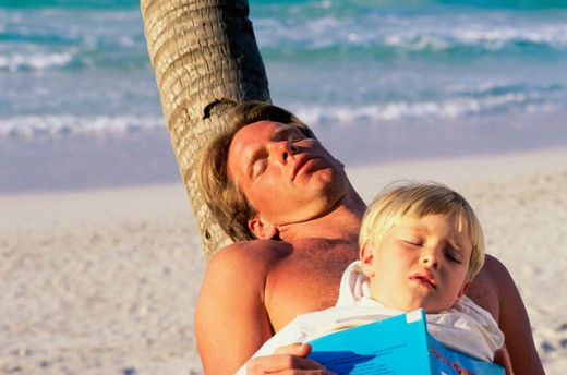 Stock Photo: 1315-244B High angle view of a father and son sleeping on the beach