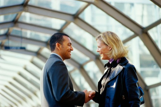 Side profile of a businessman and a businesswoman shaking hands : Stock Photo