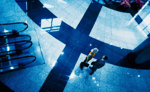 High angle view of a businessman and a businesswoman talking in a lobby : Stock Photo