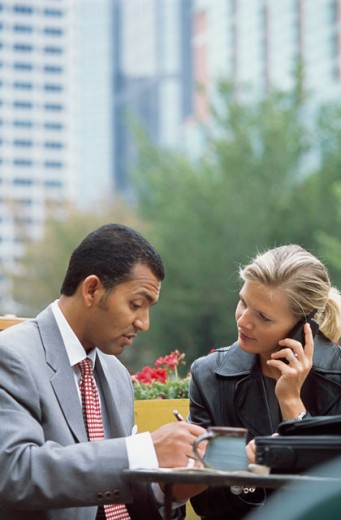 Businesswoman talking on a mobile phone with a businessman sitting beside her : Stock Photo