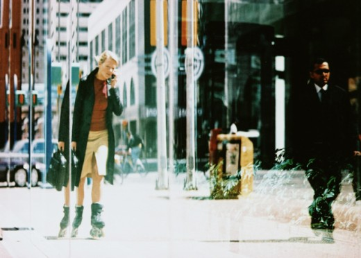 Businesswoman talking on a mobile phone and inline skating : Stock Photo