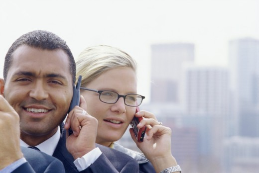 Close-up of a businessman and a businesswoman talking on a mobile phone : Stock Photo