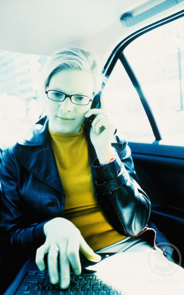 Stock Photo: 1315-431B Businesswoman talking on a mobile phone in a car