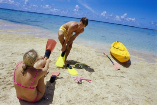 Stock Photo: 1315-486A Young couple putting on flippers on the beach