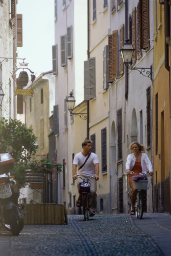 Young couple riding their bicycles on the road, Cremona, Italy : Stock Photo