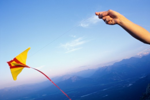Stock Photo: 1315-604 Person's hand flying a kite, Banff National Park, Alberta, Canada