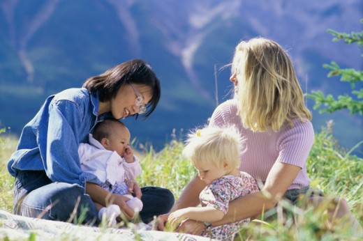 Stock Photo: 1315-644 Two mid adult women sitting with their children