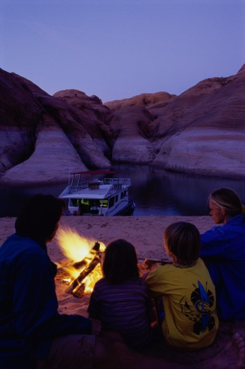 Rear view of parents with their son and a daughter at a campfire, Lake Powell, Glen Canyon National Recreation Area, Arizona-Utah Border, USA : Stock Photo