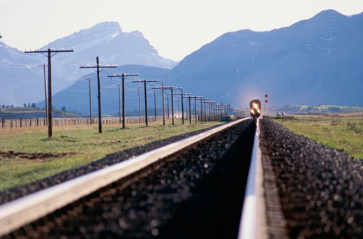 Train on a railroad track in front of mountains, Alberta, Canada : Stock Photo