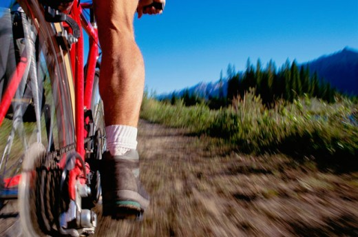 Low section view of a man mountain biking : Stock Photo