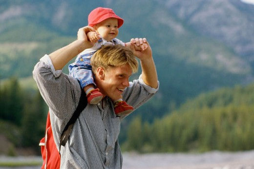 Side profile of a father carrying his daughter on his shoulders : Stock Photo