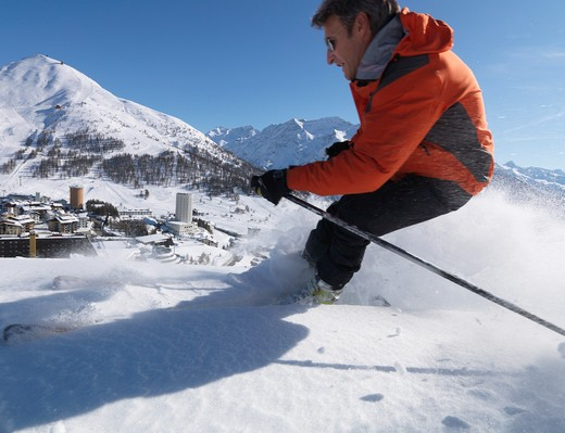 Stock Photo: 1315R-10268 Italy, Piedmont, Sestriere village and ski resort (site of 2006 winter Olympics), with skier in foreground