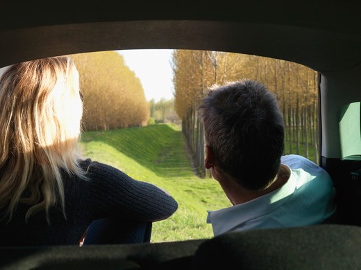Stock Photo: 1315R-10278 Italy, Piedmont, Couple look out from car interior to raised dike, planted forest