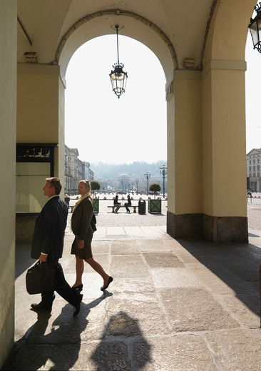 Italy, Turin, Business couple walk through porticos in front of piazza : Stock Photo