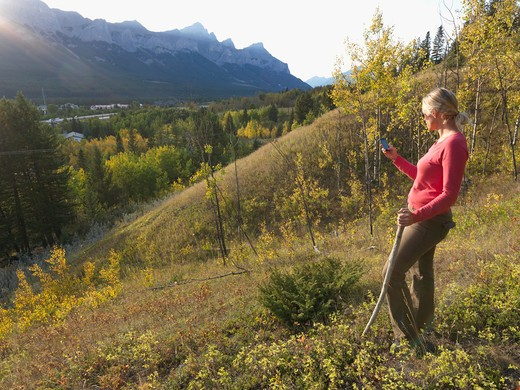 Stock Photo: 1315R-10311 Canada, Alberta, Woman sending text message on hillside above Canmore