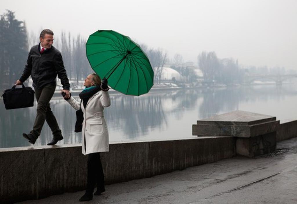 Stock Photo: 1315R-10342 Italy, Turin, Couple walking along promenade wall
