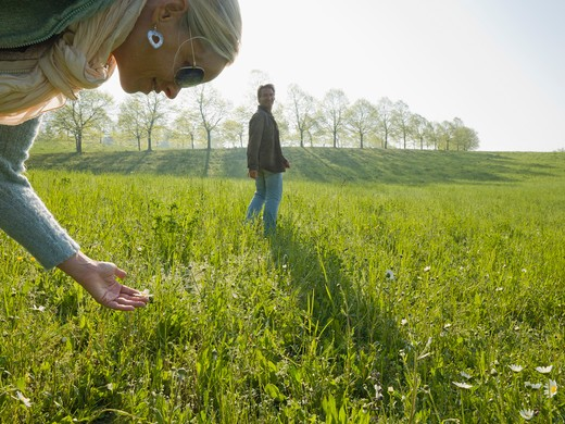 Italy, Piedmont, Woman looking at flower in meadow, man in background : Stock Photo