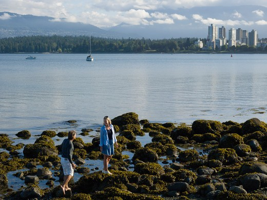 Canada, British Columbia, Vancouver, Couple walking through algae covered tidal rocks, downtown skyline in background : Stock Photo