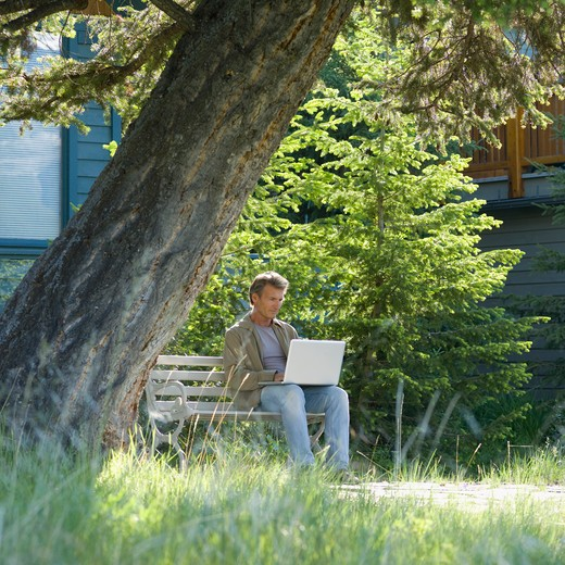 Canada, Alberta, Canmore, Man using laptop computer in front of mountain home : Stock Photo