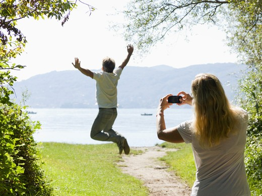 Italy, Piedmont, Lake Maggiore, Woman taking picture of man jumping for joy : Stock Photo