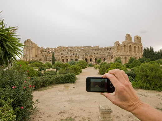 Stock Photo: 1315R-10440 Tunisia, El Djem, Woman's hand taking picture of distant coliseum with cell phone