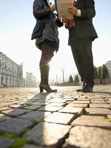 Stock Photo: 1315R-10465 Italy, Piedmont, Turin, Low section of business couple examining documents in downtown piazza