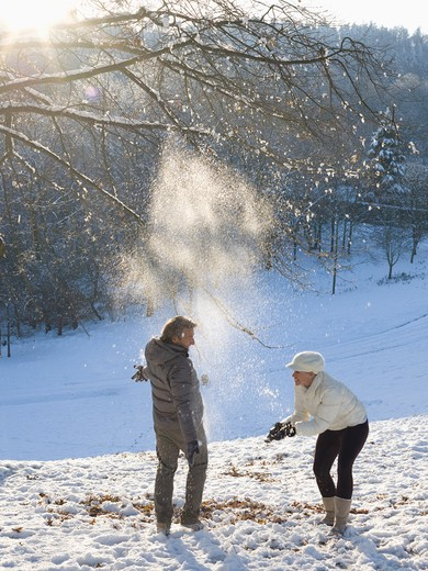Italy, Piedmont, Couple throwing snow overhead in snowy park : Stock Photo
