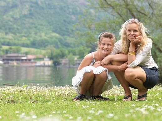 Stock Photo: 1315R-1258 Italy, Piedmont, Mother and daughter crouching in meadow near lake