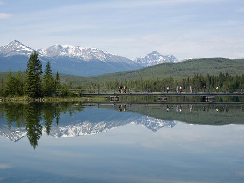 Canada, Alberta, Jasper National Park, Pyramid Lake, people crossing bridge : Stock Photo