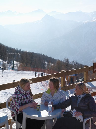 Italy, Piedmont, Bardonecchia, teenage girls and mother having lunch at outdoor cafe : Stock Photo