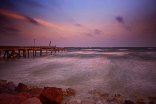 Stock Photo: 1317-1220 USA, Texas, Galveston, Early morning light with storm clouds at Fishing pier on Seawall Boulevard