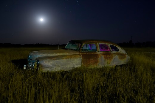 Abandoned vintage car in a field at night, USA : Stock Photo