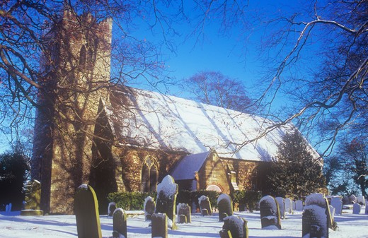 United Kingdom, Norfolk, Stokesby, English thatched flint church and churchyard with beech trees under snow : Stock Photo