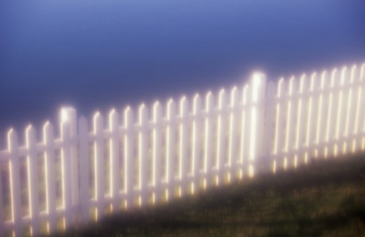 Stock Photo: 1318-1480 Picket fence in evening light with water behind