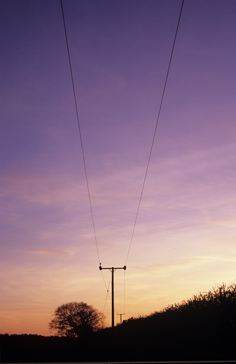 United Kingdom, Norfolk, Winter sunset sky over country lane with power lines : Stock Photo