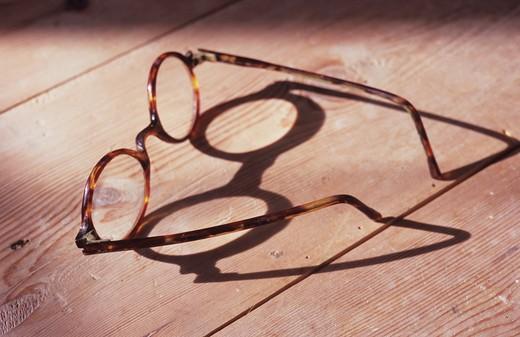 Stock Photo: 1318R-1472 UK, England, Norfolk, Pair of 1930s reading glasses with tortoiseshell frames on wooden table
